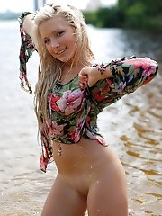 Marvelous blond filly with juicy shapes and big natural boobs poses naked by the river.